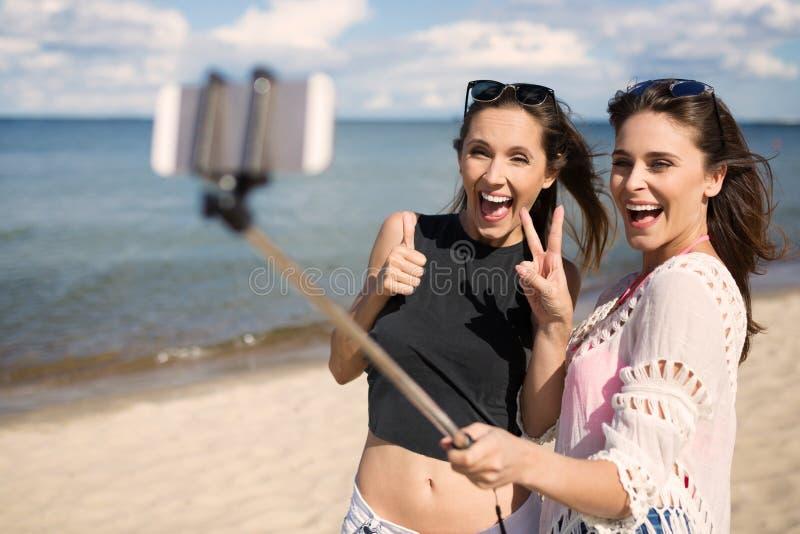 Två lyckliga kvinnliga vänner som tar selfie på stranden royaltyfria bilder