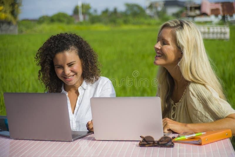 Två lyckliga kvinnliga vänner som utomhus arbetar på det härliga internetkafét med den caucasian kvinnan för bärbar datordator oc fotografering för bildbyråer