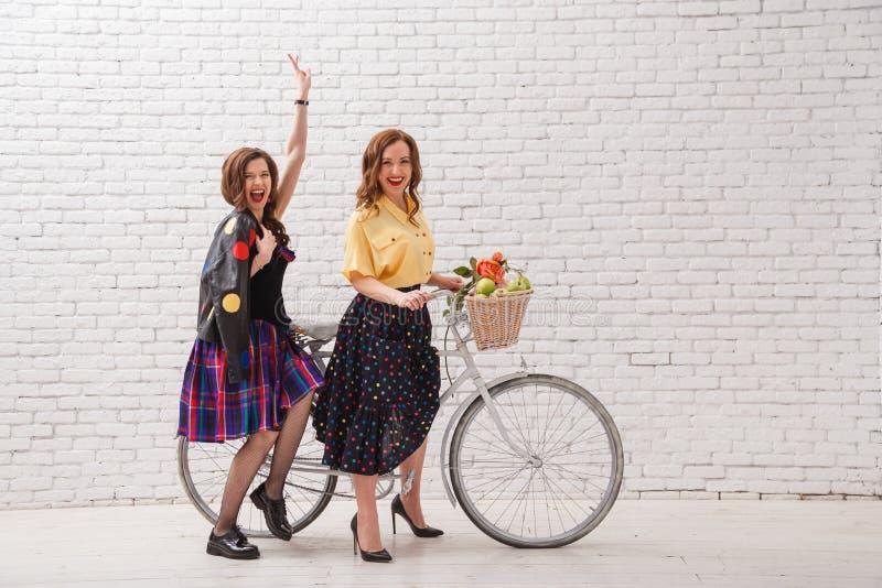 Två lyckliga kvinnor i sommarklänningar rider tillsammans på en retro cykel, och gesten räcker framåtriktat fotografering för bildbyråer
