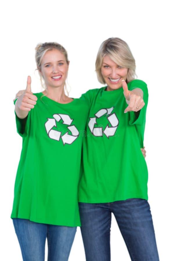 Två lyckliga kvinnor som bär gröna återvinningtshirts som ger upp tummar fotografering för bildbyråer