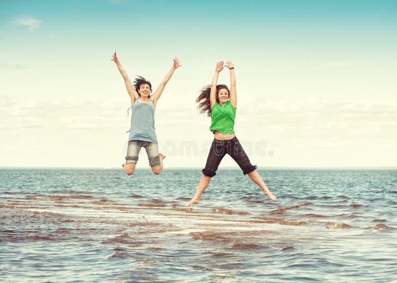 Två lyckliga kvinnor som hoppar i vattnet av havet arkivfoto