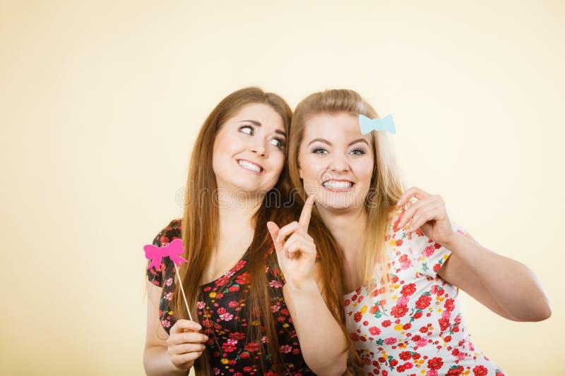 Två lyckliga kvinnor som rymmer karnevalaccessoies på pinnen arkivbild