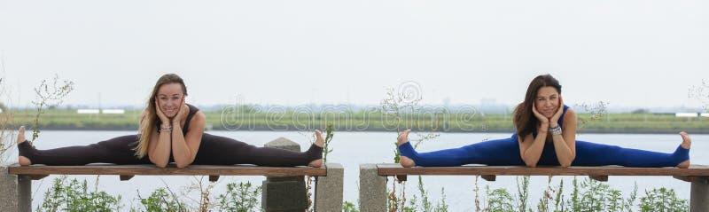 Två lyckliga le blonda flickor som tillsammans gör yogaövning i morgon i härligt bergsjölandskap Yogareträtt, sport royaltyfria foton