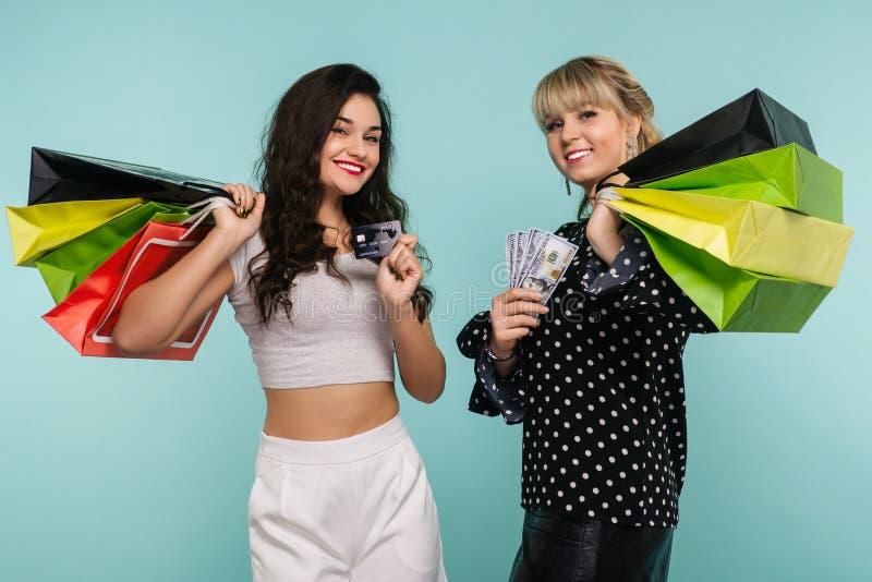 Två lyckliga le flickor med en kreditkort och en packe av dollar står med shoppingpåsar royaltyfri fotografi