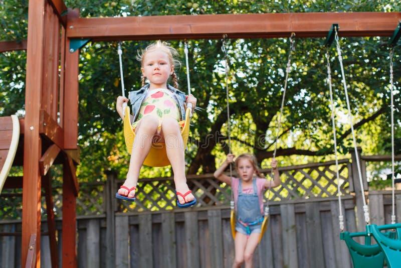 Två lyckliga le små flickor på gunga på trädgårdlekplats utanför på sommardag royaltyfria foton
