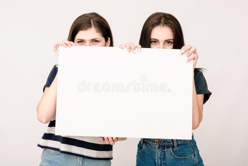 Två lyckliga le unga kvinnor som att bry sig den stora tomma skylten royaltyfri foto