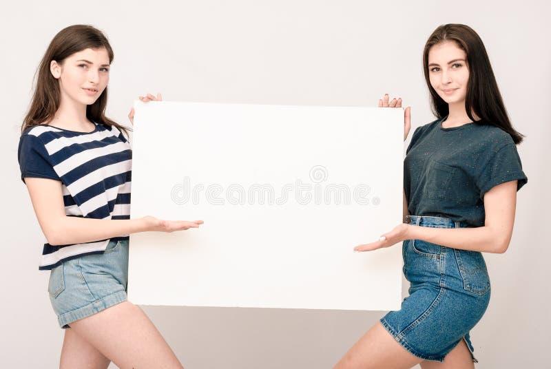 Två lyckliga le unga kvinnor som att bry sig den stora tomma skylten arkivbild
