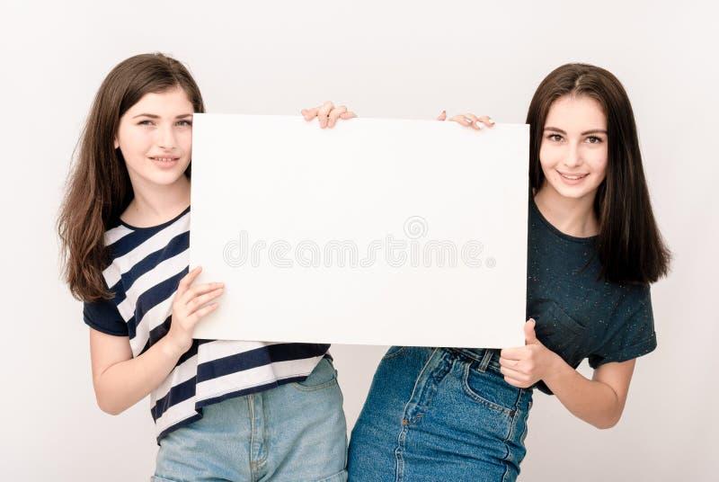 Två lyckliga le unga kvinnor som att bry sig den stora tomma skylten royaltyfria foton