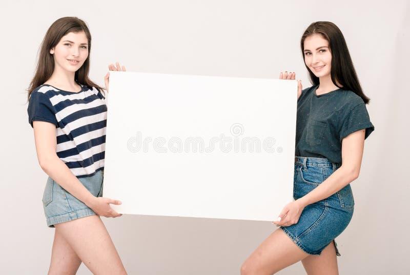 Två lyckliga le unga kvinnor som bär den stora tomma skylten royaltyfria foton
