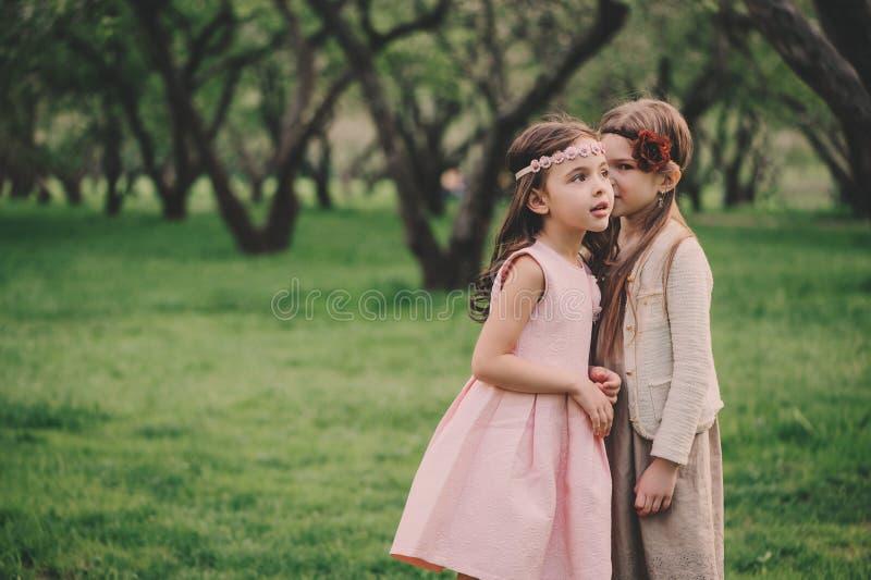 Två lyckliga lilla flickvänner som väljer blommor i vårträdgård Systrar som tillsammans spenderar utomhus- tid arkivfoto