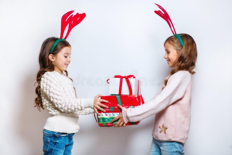 Två lyckliga lilla le flickor med julgåvaaskar Julfilial och klockor Le roliga systrar i hjorthorn in royaltyfri foto