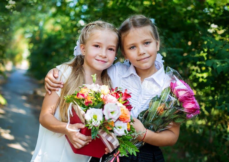 Två lyckliga lilla skolflickor med buketter arkivfoto