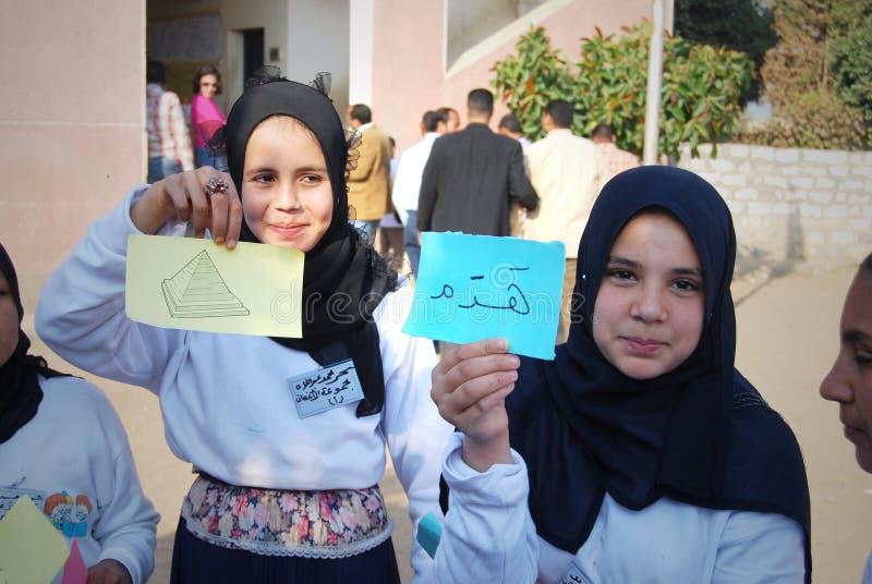 Två lyckliga muslimska flickor som rymmer arabiskaord royaltyfria bilder