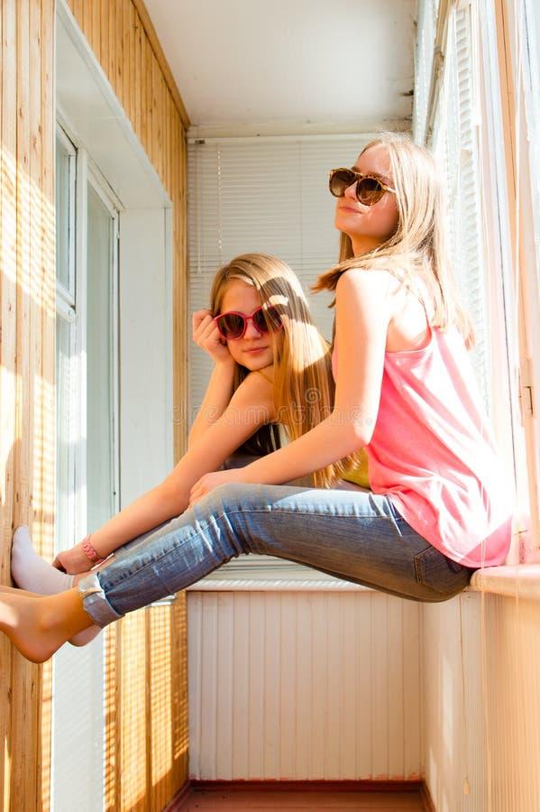 Två lyckliga nätta tonårs- flickor i solglasögon arkivfoto