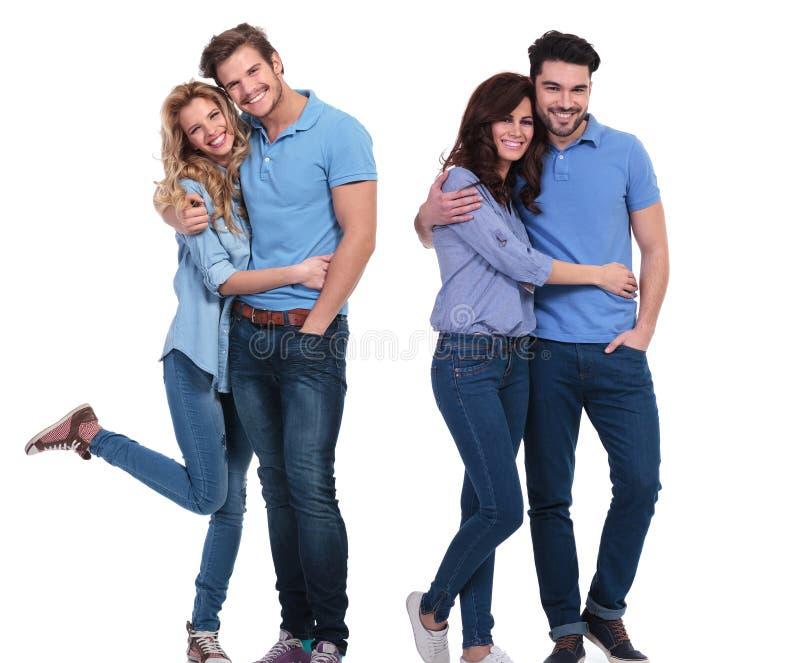 Två lyckliga par av ungt tillfälligt folk som står omfamnat arkivfoton