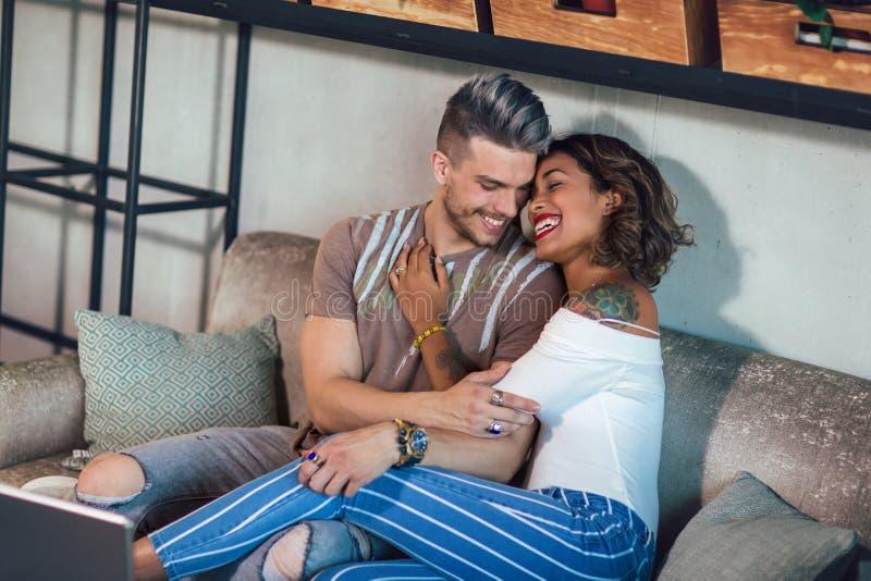 Två lyckliga par för blandat lopp som har gyckel på coffee shop royaltyfria foton