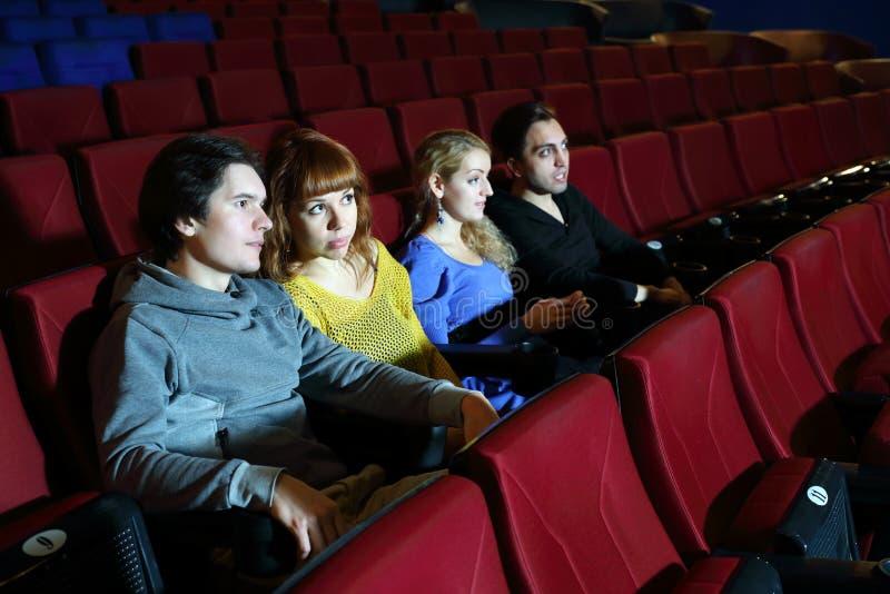 Två lyckliga par ser film och talar i bioteater fotografering för bildbyråer
