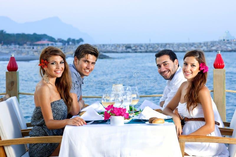 Två lyckliga par som har matställen på sjösidan royaltyfria foton