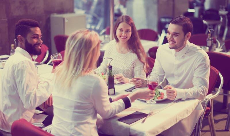 Två lyckliga par som sitter på den utomhus- restaurangen royaltyfri fotografi