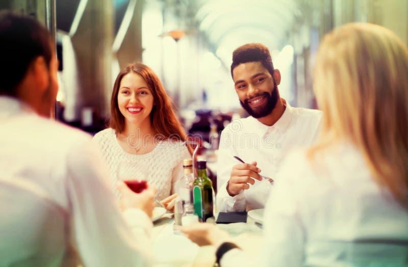 Två lyckliga par som sitter på den utomhus- restaurangen royaltyfri foto