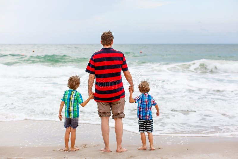 Två lyckliga pojkar för små ungar och faderanseende på stranden av havet och se på horisont på stormig dag Familj farsa royaltyfri fotografi