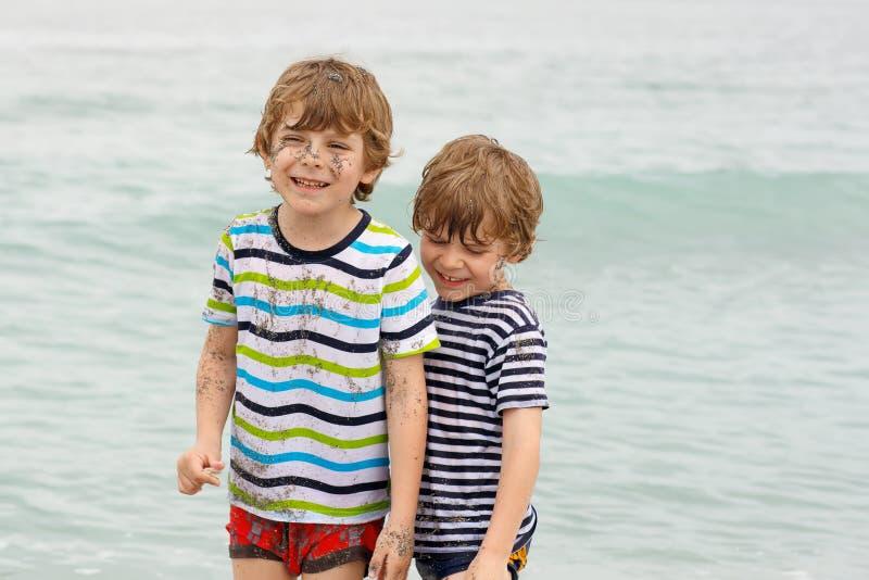 Två lyckliga pojkar för små ungar som kör på stranden av havet Roliga barn, syskon, kopplar samman och bästa vänframställning royaltyfria bilder