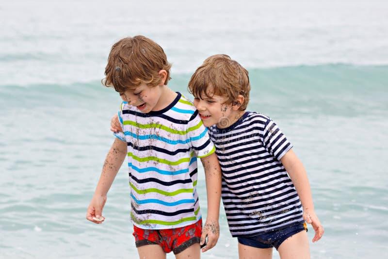 Två lyckliga pojkar för små ungar som kör på stranden av havet Roliga barn, syskon, kopplar samman och bästa vänframställning royaltyfri bild