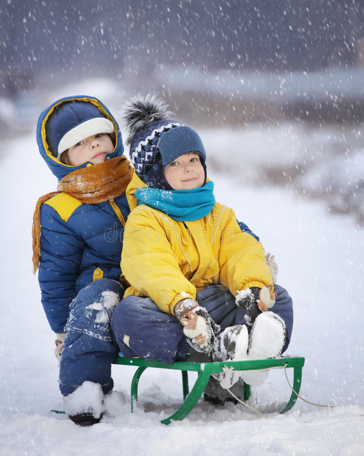 Två lyckliga pojkar på släden royaltyfri bild