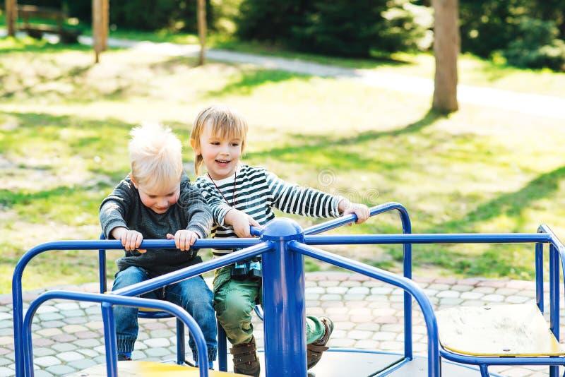 Två lyckliga pojkar som spelar på lekplats i en parkera fotografering för bildbyråer