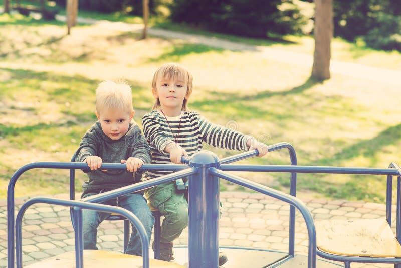 Två lyckliga pojkar som spelar på lekplats i en parkera tonat arkivbild