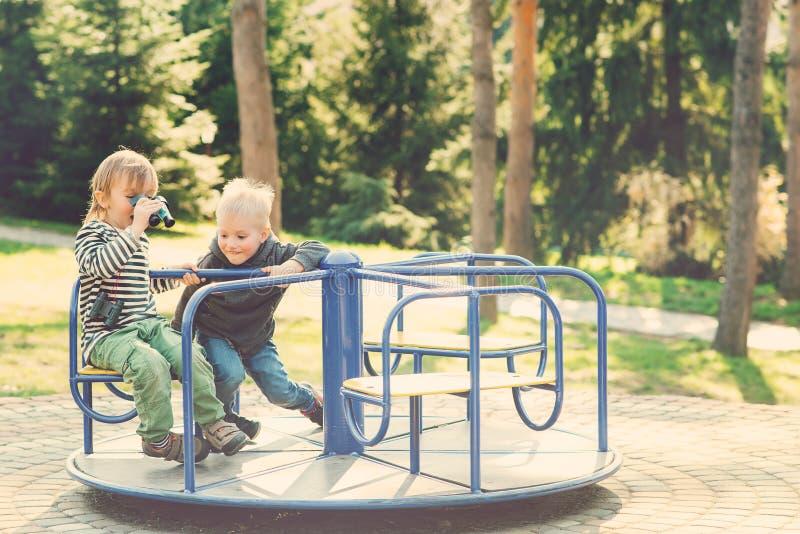 Två lyckliga pojkar som spelar på lekplats i en parkera tonat arkivfoton