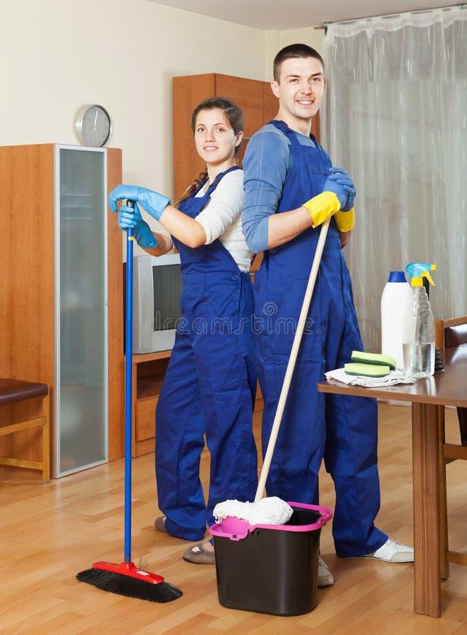Två lyckliga rengöringsmedel som gör ren golvet royaltyfria foton