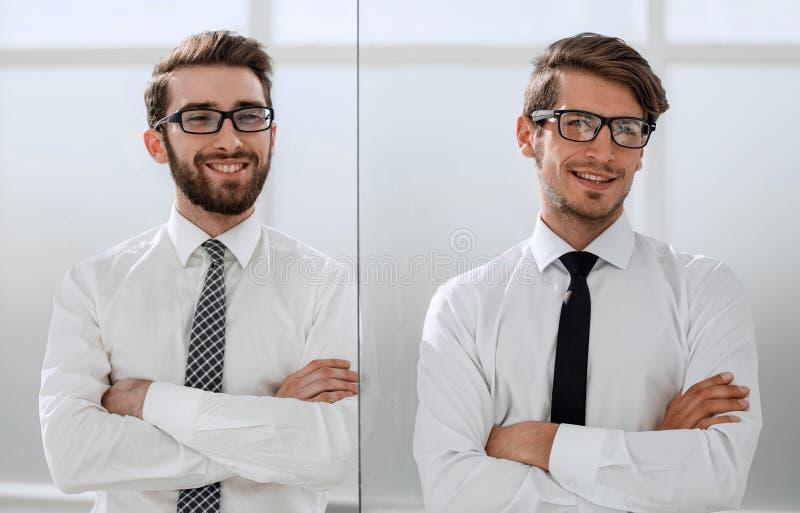 Två lyckliga säkra unga affärsmän som står med armar som i regeringsställning korsas arkivfoton