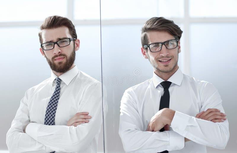Två lyckliga säkra unga affärsmän som står med armar som i regeringsställning korsas royaltyfria bilder