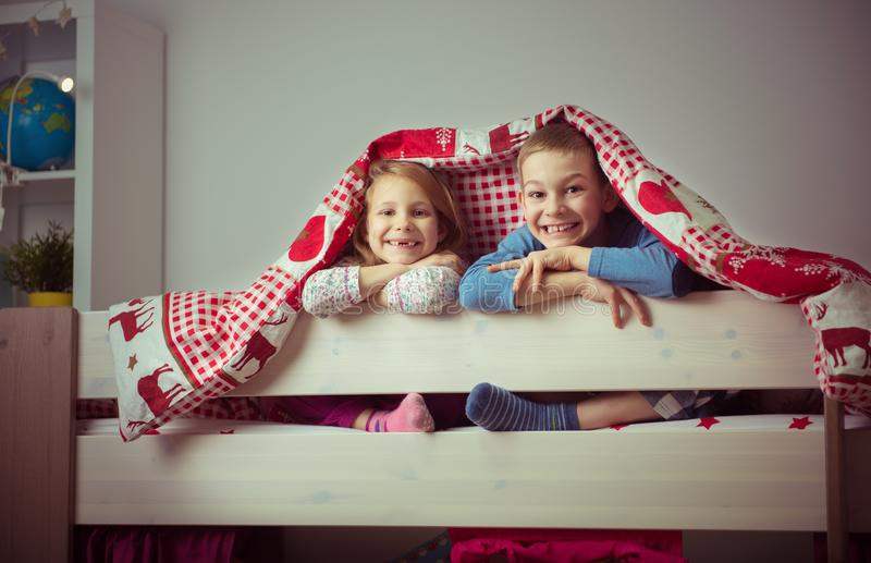 Två lyckliga siblingbarn som har gyckel i britssäng arkivbilder