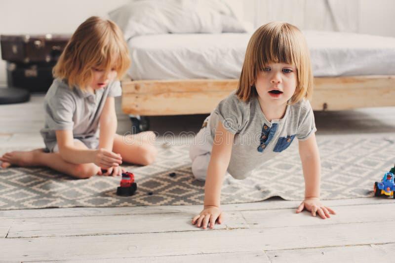 Två lyckliga siblingpojkar som tillsammans hemma spelar med leksakbilar fotografering för bildbyråer