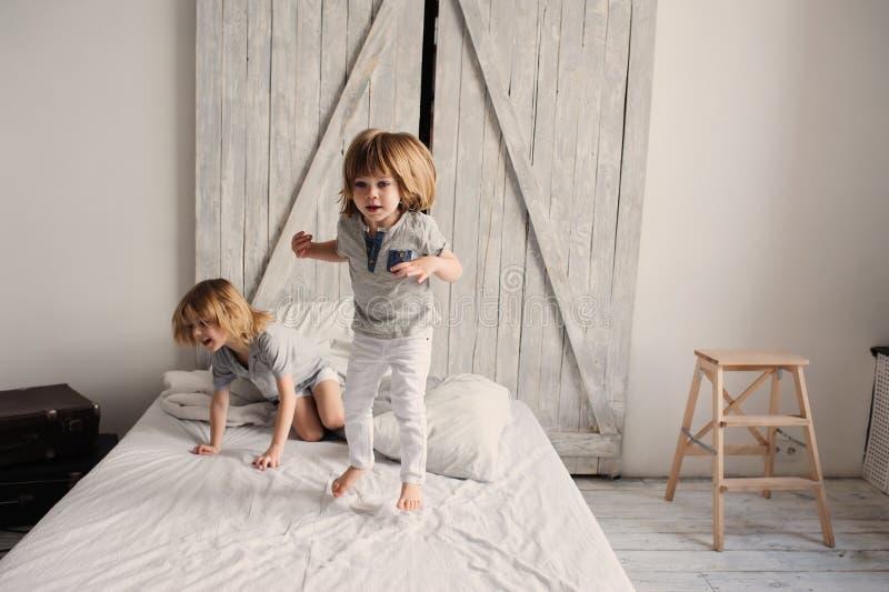 Två lyckliga siblingpojkar som tillsammans hemma spelar på säng royaltyfri foto