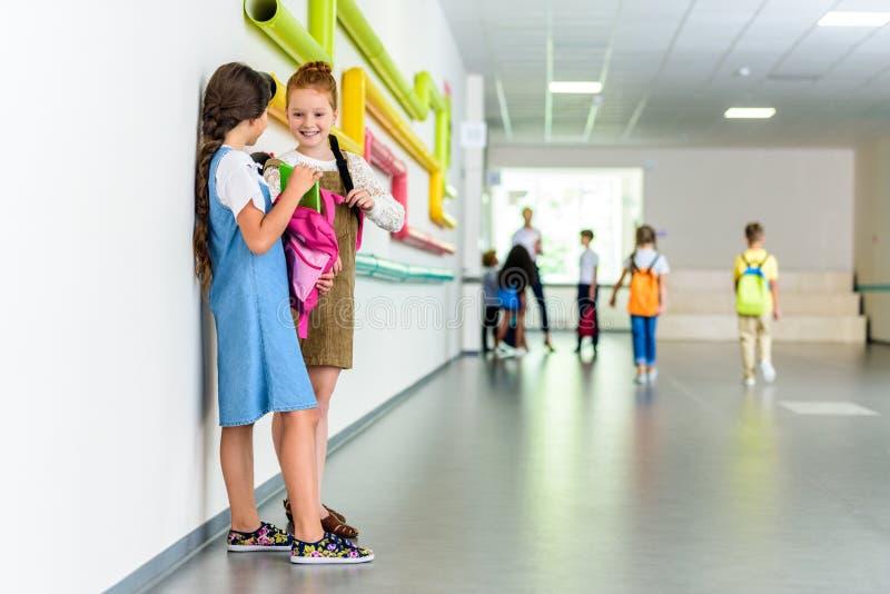 två lyckliga skolflickor som pratar på skolakorridoren arkivbild