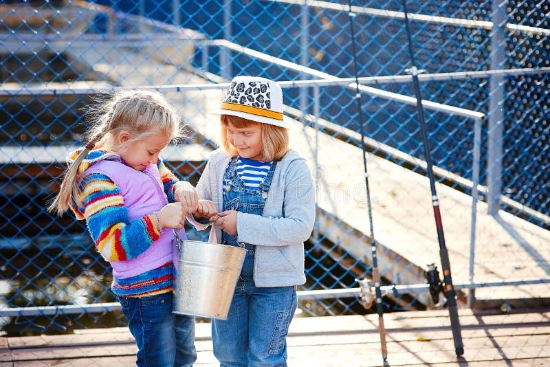 Två lyckliga skratta barn med metspön och en hink på en fisketur på en träponton på en fisklantgård royaltyfri fotografi