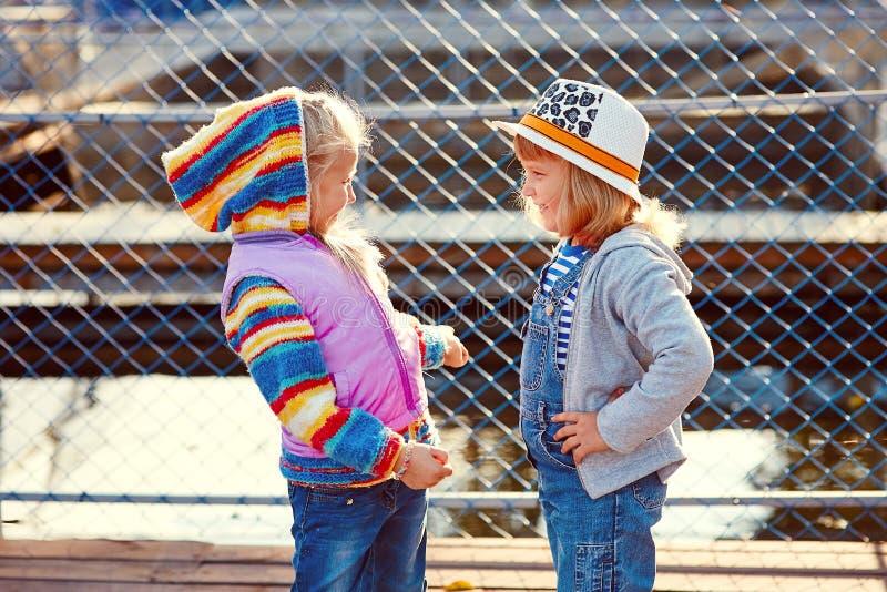 Två lyckliga skratta barn med metspön och en hink på en fisketur på en träponton på en fisklantgård arkivfoton