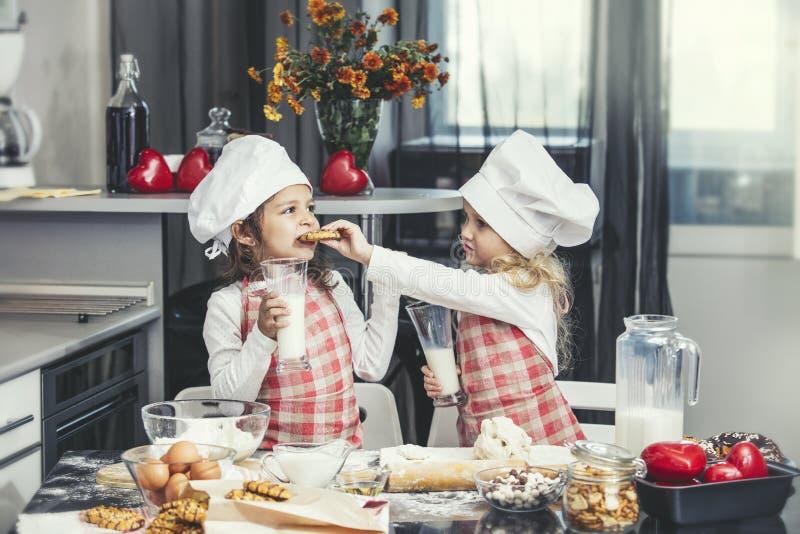 Två lyckliga små behandla som ett barn flickan som att dricka mjölkar, och lagar mat på tabellen I fotografering för bildbyråer