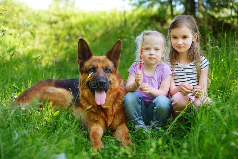 Två lyckliga små flickor och deras stora hund royaltyfri fotografi