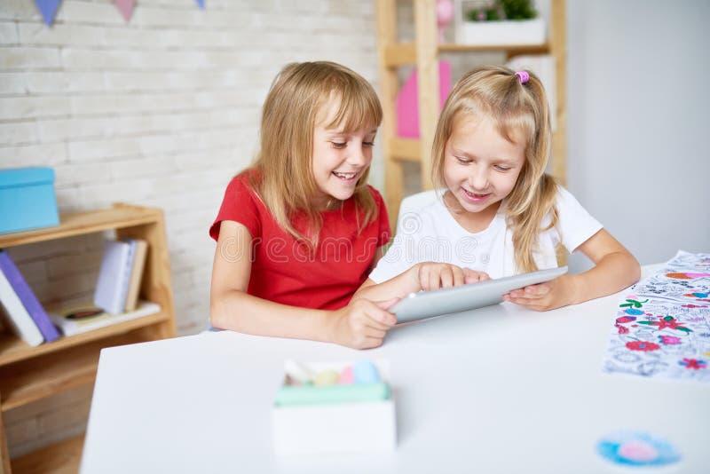 Två lyckliga små flickor som använder den Digital minnestavlan royaltyfri fotografi