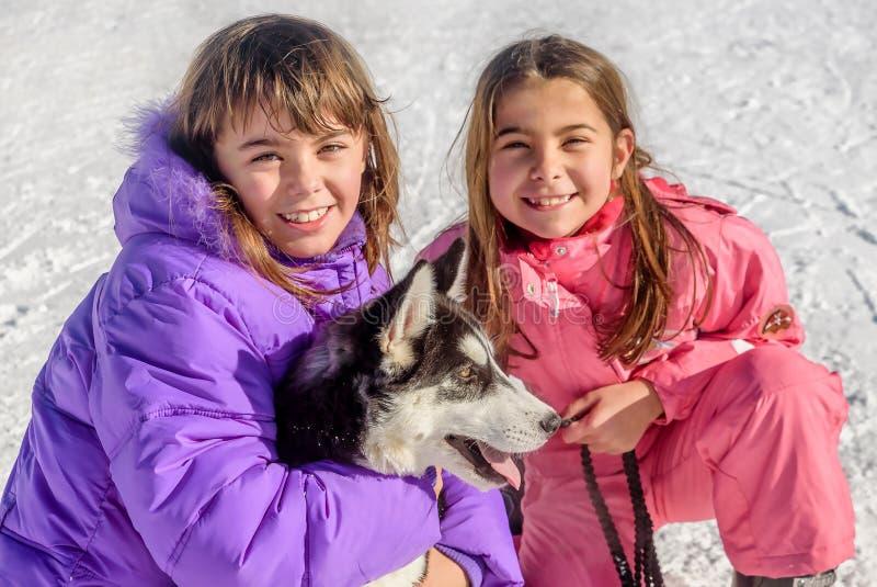 Två lyckliga små flickor som rymmer valphunden skrovlig på snön royaltyfria bilder