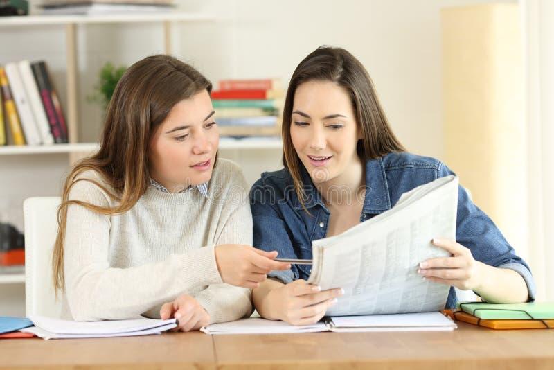 Två lyckliga studenter som talar om en tidningsnyheterna royaltyfria foton