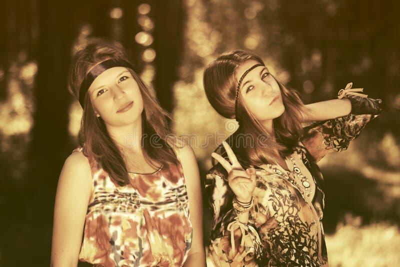 Två lyckliga tonåriga flickor som går i sommarskog arkivfoton