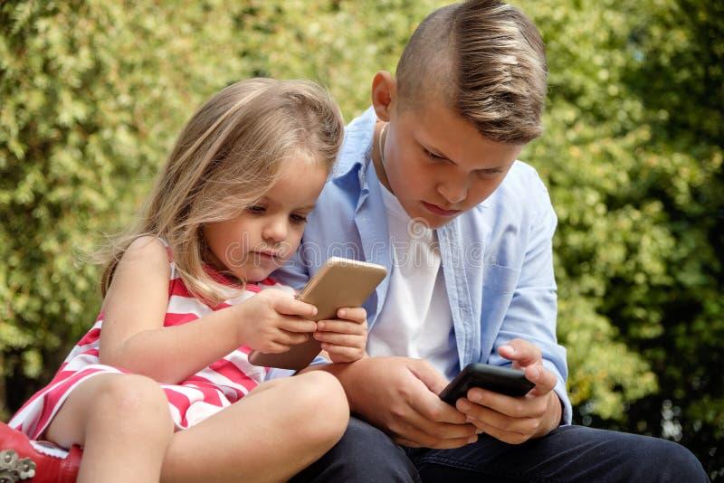 Två lyckliga tonårs- vänner som använder på mobiltelefonen, medan koppla av i, parkerar Problem av modern ungdom, sociala nätverk royaltyfria bilder