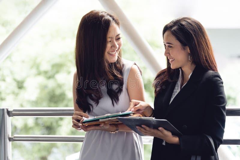 Två lyckliga unga asiatiska affärskvinnor som ser in i dokumentmappmappen för analysering av vinst- eller försäljningsavbrottet p arkivbild