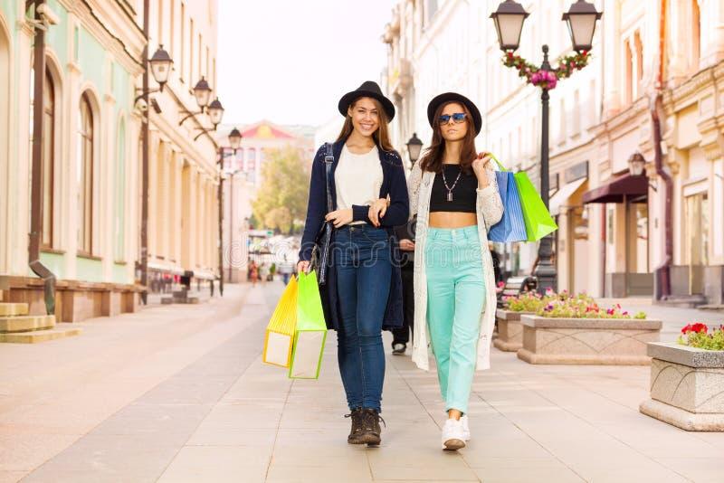 Två lyckliga unga kvinnor som bär shoppingpåsar royaltyfri fotografi