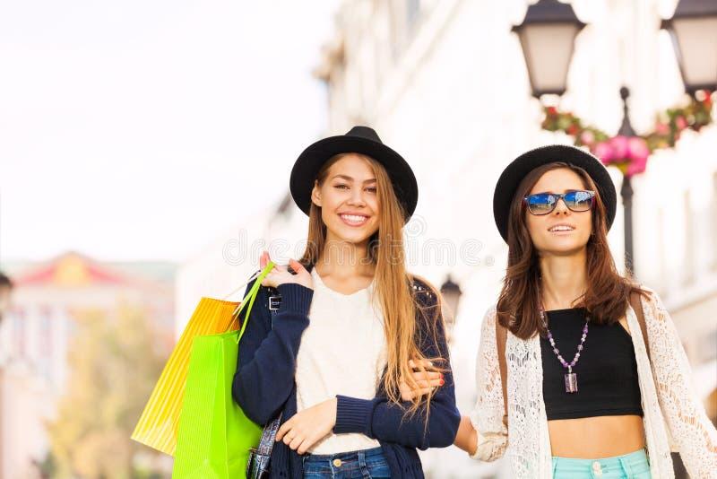 Två lyckliga unga kvinnor som går med shoppingpåsar royaltyfri foto